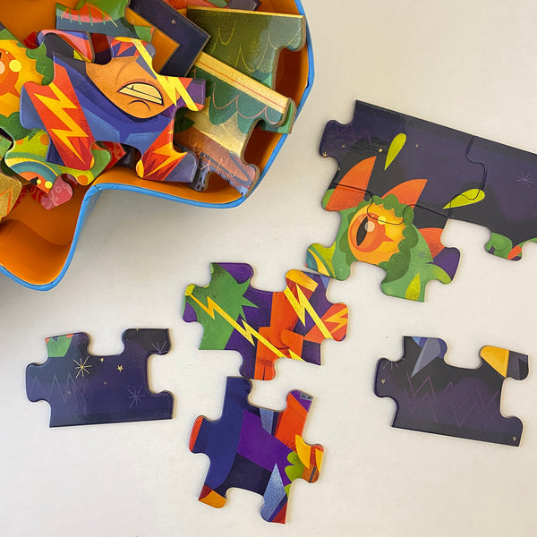 close up of jigsaw pieces scattered beside the box on w hite background. three pieces are joined and four are loose.