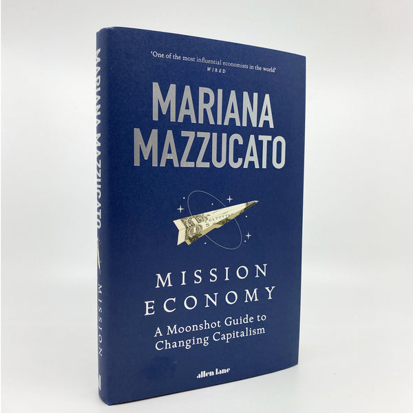 image of the book standing upright in front of a white background angled to the right. There is a navy blue with a dollar bill folded in to the shape of a rocket and surrounded by a ring and stars. the title and authors name are on the cover in white