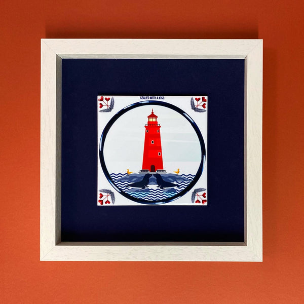 ceramic tile with red lighthouse and two seals kissing in the sea in the foreground. behind the tile is a navy blue background and it is in a white frame. red display background