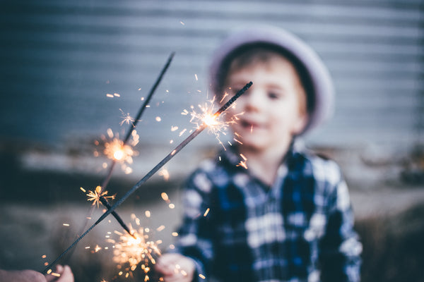Young boy wearing a plaid shirt and a hat holding a lit sparkler