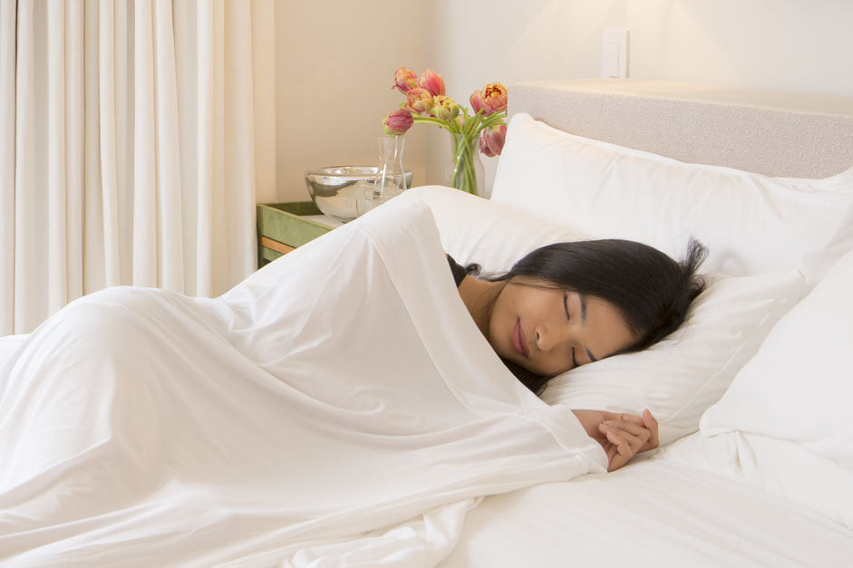 Girl sleeping in bed with light sheets