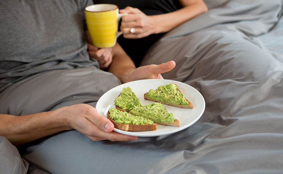 Couple eating avocado toast in bed