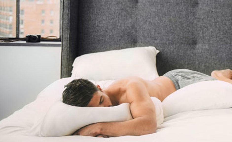 Man sleeping in a bed on his stomach