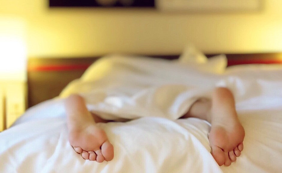 feet hanging off of a bed