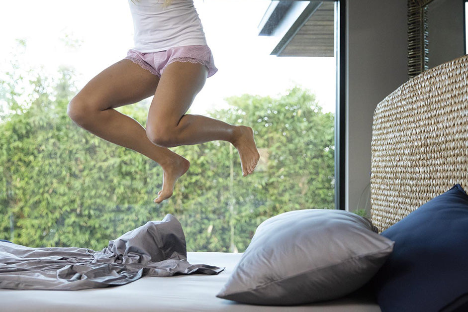 lady jumping on the bed