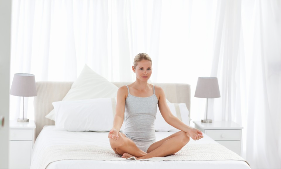 Woman doing the Adept's Yoga Pose in bed