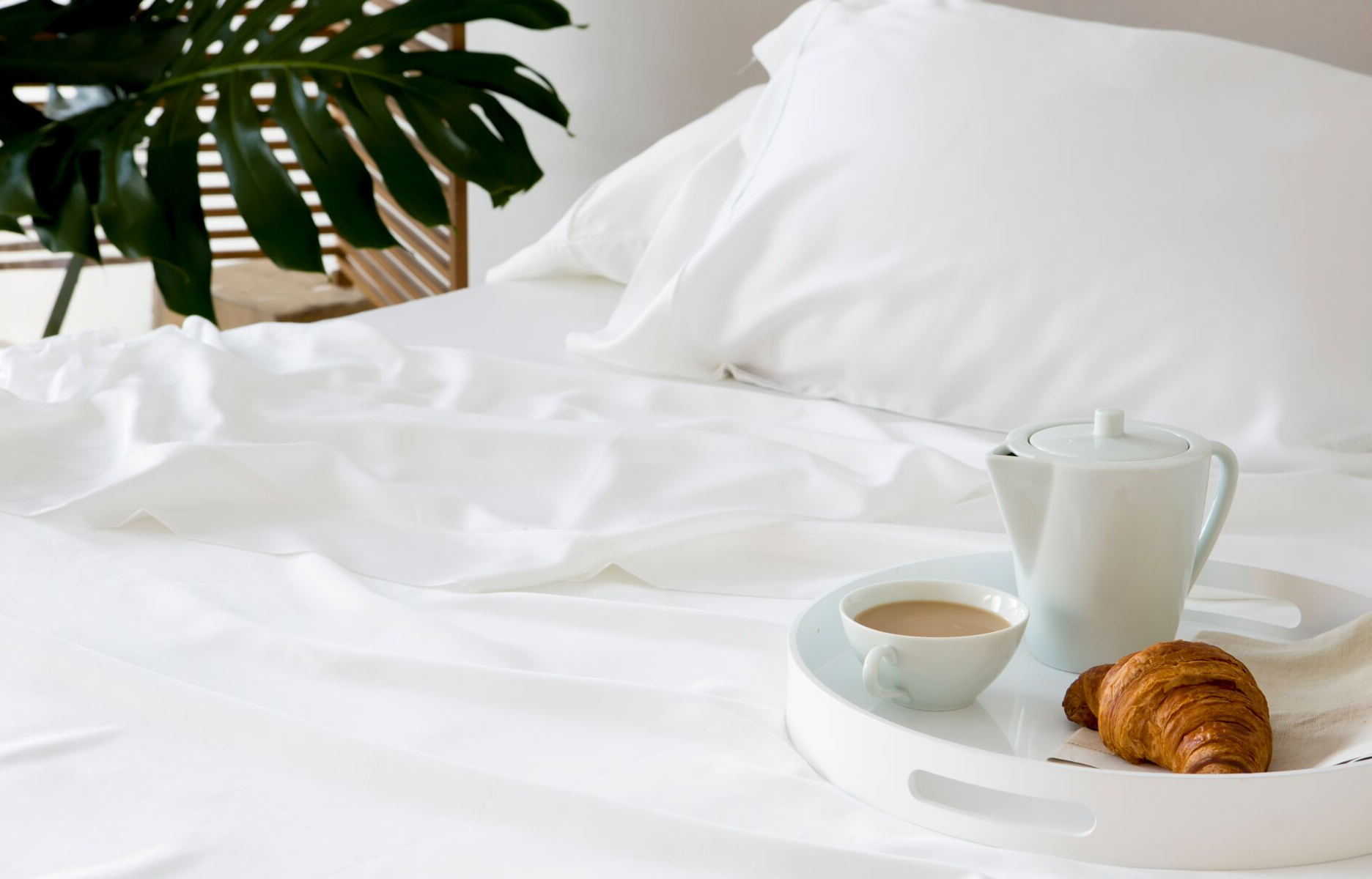 bed with coffee and croissant