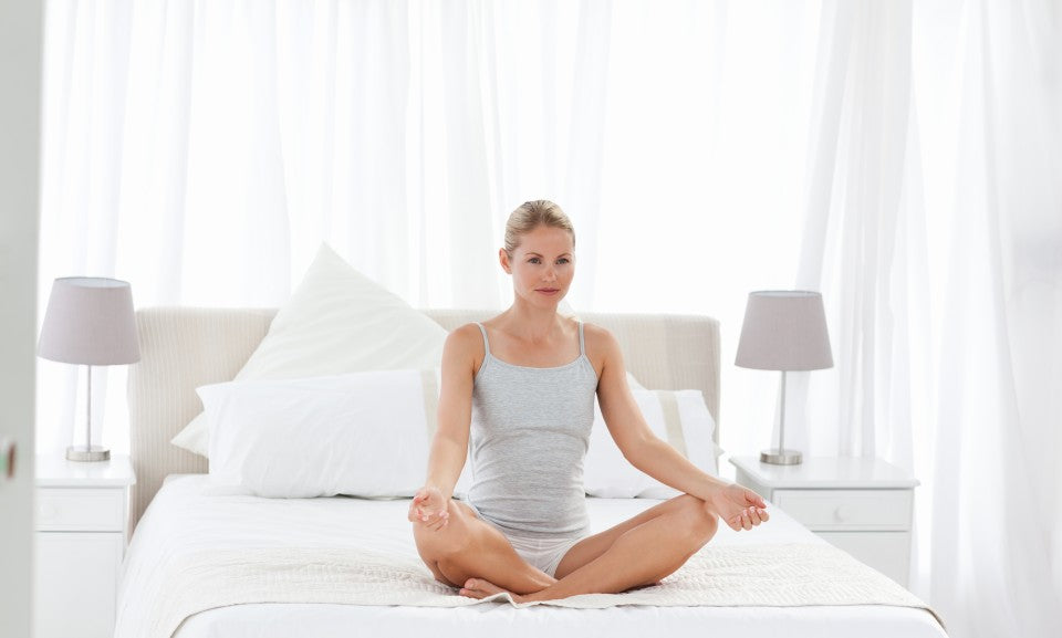 Woman sitting in bed meditating