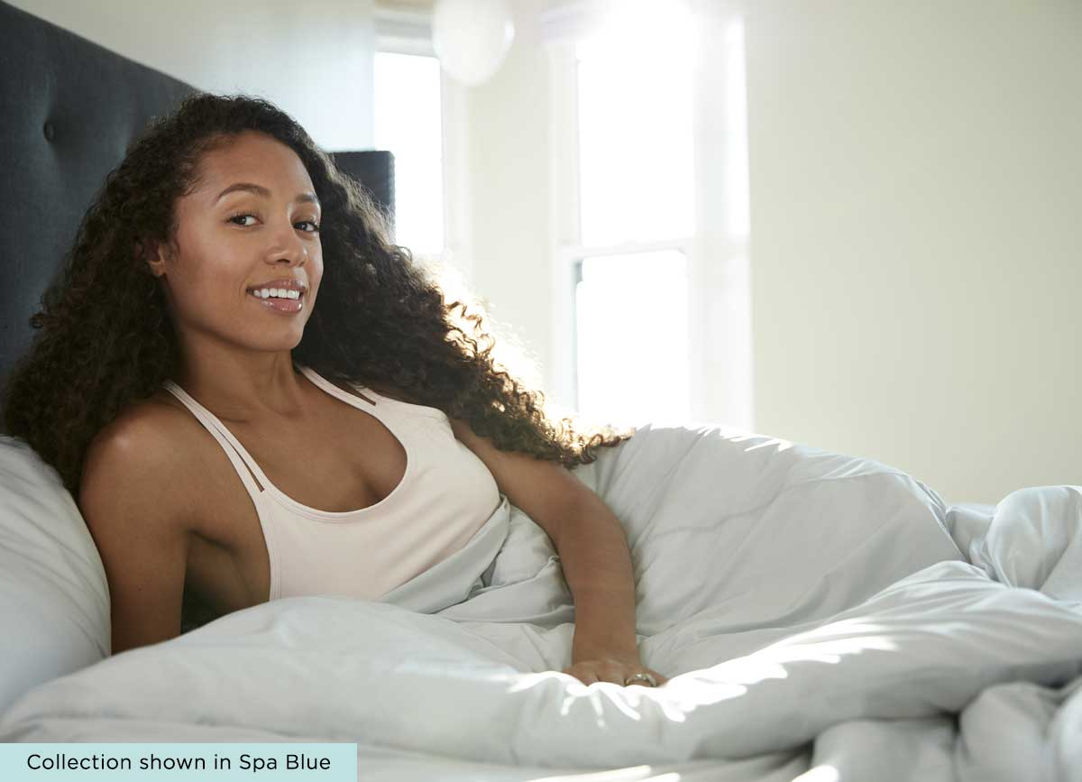 Lifestyle of Midnight Label Duvet Cover shown on bed with model  #choose-your-color_mist-gray