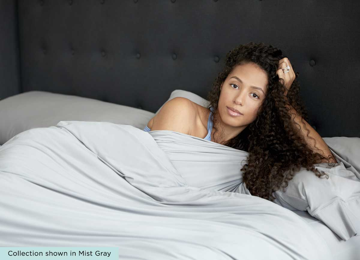 Lifestyle of Midnight Label Duvet Cover shown on bed with model  #choose-your-color_porcelain