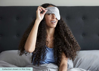 midnight label-sleep mask + travel pouch - mist gray color on model in bed with one eye winking