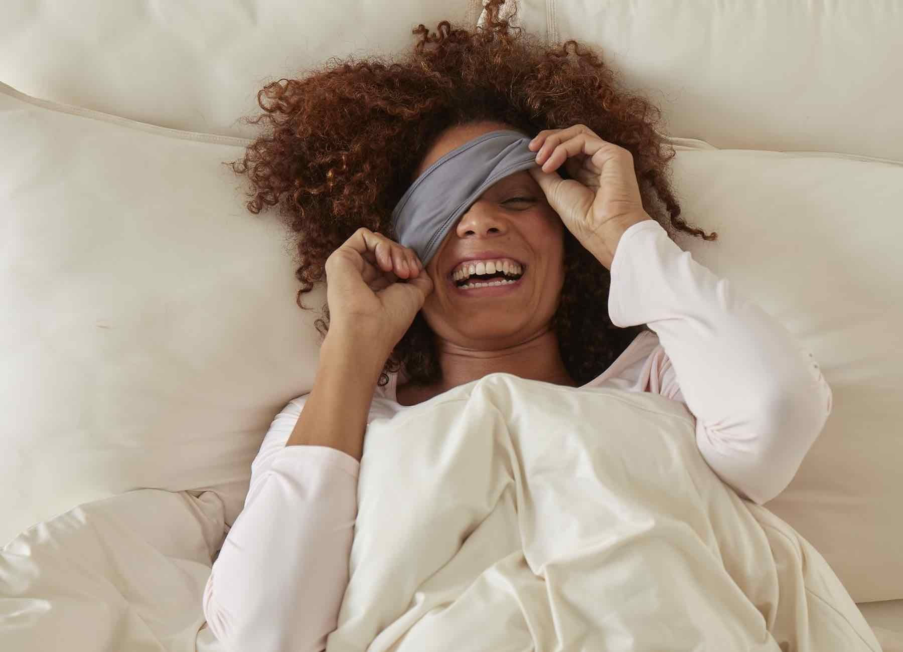 SHEEX Sleep Mask in Graphite on model in bed covering one eye with smile