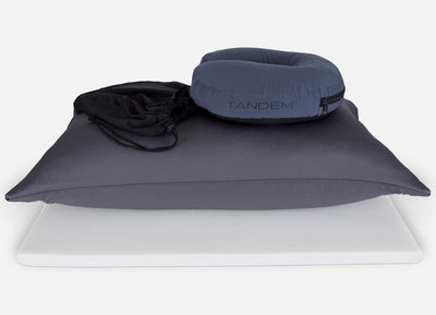 TANDEM Travel Pillow shown with drawstring carrying pouch on a pillow in charcoal on white background