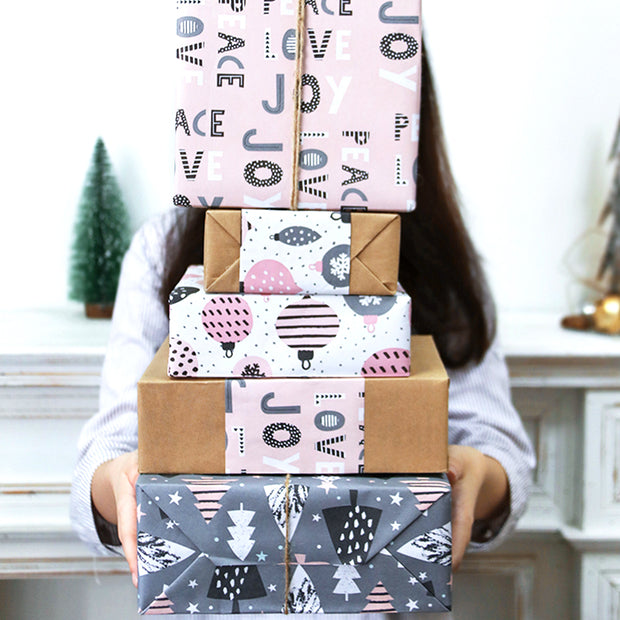 Woman holding a stack of pink and grey wrapped gifts
