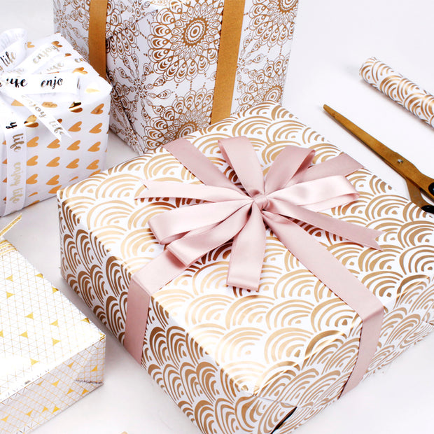 Gold geometric gift box wrapped with a rose gold gift bow
