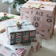 Collection of pink and grey Christmas theme gift wrapped boxes on a table
