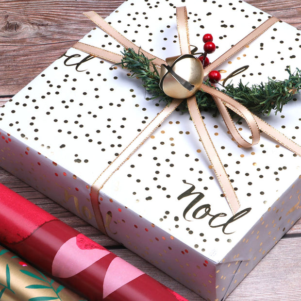White and metallic gold polka dot wrapped gift with satin bow and bell