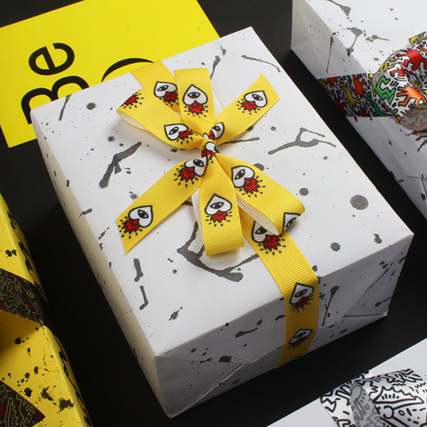 White gift box wrapped with yellow ribbon