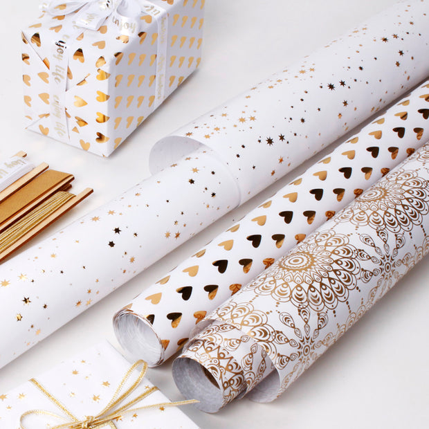 Collection of various white and gold wrapping paper rolls