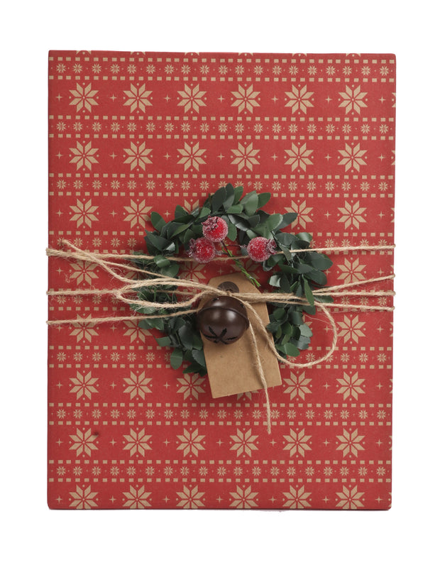 Red Kraft gift wrapped box with a square gift tag, wreath and twine