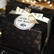 Black and gold wrapped gift with white satin bow