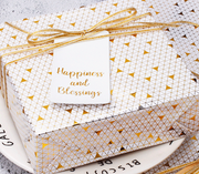 White and gold geometric gift box wrapped with a thin, gold gift bow