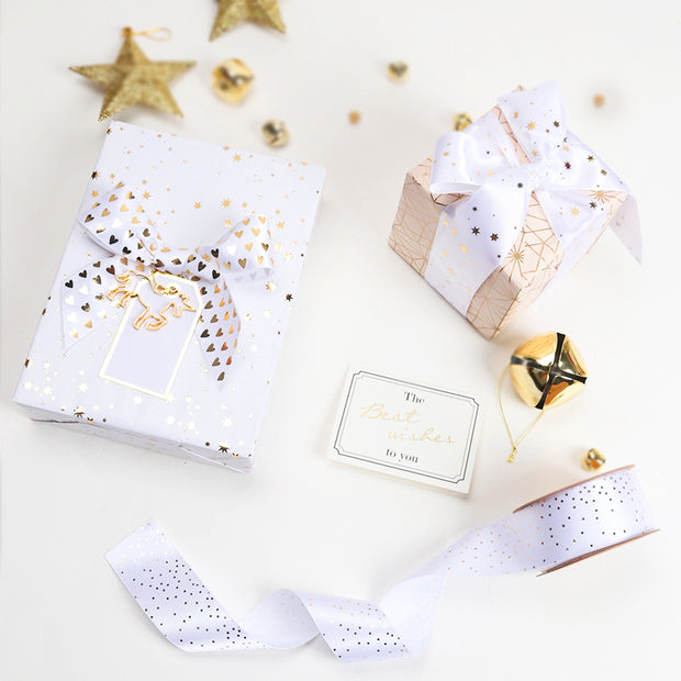 Gift boxes wrapped with white and gold satin ribbon