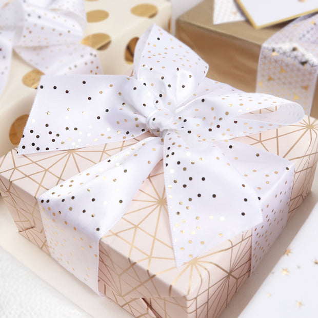 Gift box wrapped with white and gold a satin ribbon
