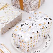 White and metallic gold print wrapped gifts