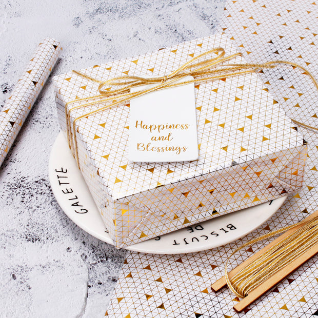 White and metallic gold geometric print wrapped gift