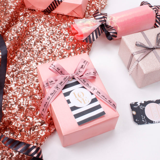 Pink wrapped gift with a black and white stripe gift tag