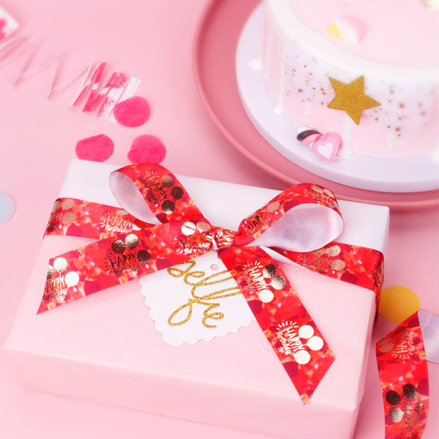 Pink wrapped gift with a red and gold foil ribbon