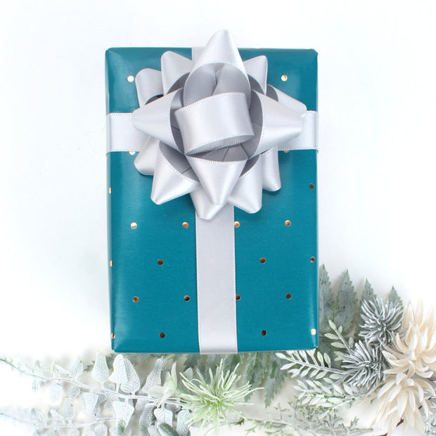 Teal gift box with polka dots, wrapped with a silver gift bow