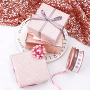 White glitter wrapped gift with a metallic ribbon