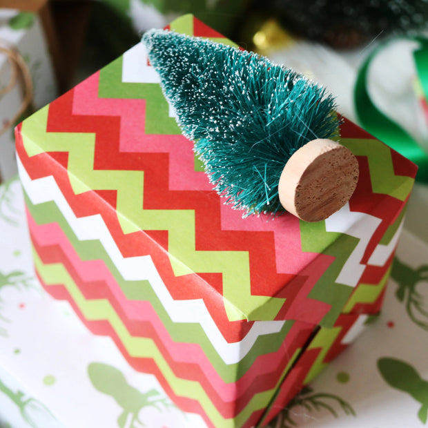 Red chevron style print wrapped gift with a fake pine tree on top