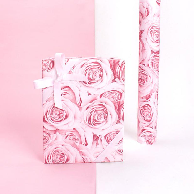 Pink rose pattern wrapped gift and wrapping paper roll