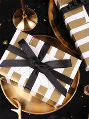 Gold stripe gift box with a black gift bow