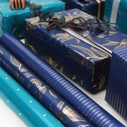 Dark blue and gold wrapping paper rolls next to gift boxes