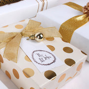Gold gift box with polka dots wrapped with a gold gift bow