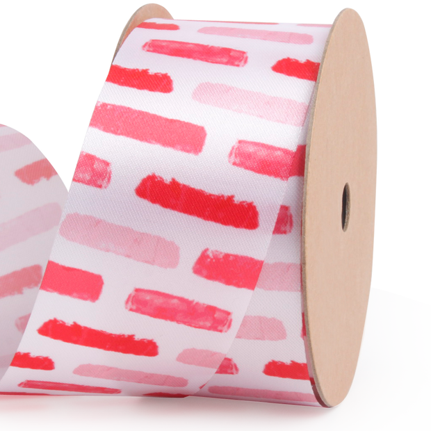 25 millimeter white satin ribbon printed with red and pink brushstrokes