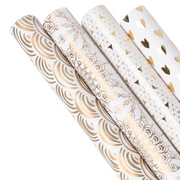 Four white and gold wrapping paper rolls