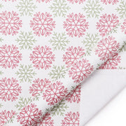 White wrapping paper printed with red and green snowflakes