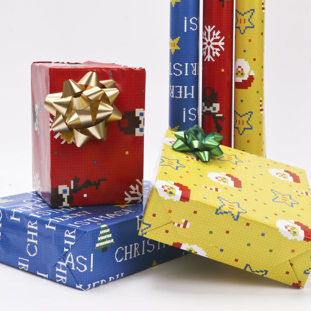 Red, yellow and blue gift boxes wrapped with gold and green gift bows in front of wrapping paper rolls
