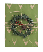 Green and beige reindeer kraft wrapped gift with twine bells