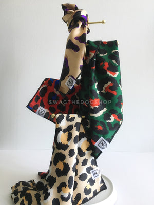 Take an advantage of 3 for $30 deal. 4 Fierce Print Swagdana Scarves displayed hanging. 1-Fierce Beige with Purple. 2-Fierce Forest Green with Red. 3-Fierce Vibrant Red with Blue. 4. Fierce Beige with Yellow. Dog Bandana. Dog Scarf
