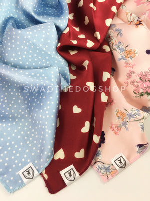 Take an advantage of 3 for $30 deal. 3 Blue/Red/Pink Color Theme Swagdana Scarves displayed. 1-Polka Itty Bitty Powdered Blue. 2-Full of Heart Burgundy Cream. 3-Pink Wild Flower. Dog Bandana. Dog Scarf