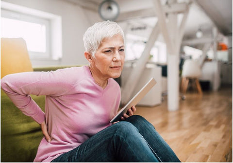 an older woman suffering form back pain