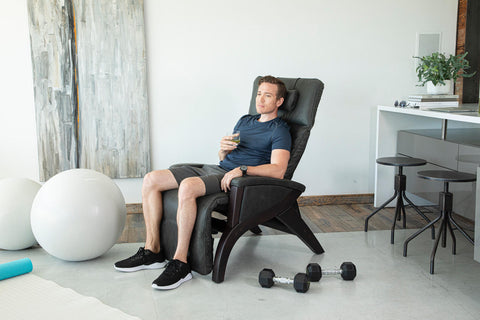 a man using a zero gravity chair for his workout
