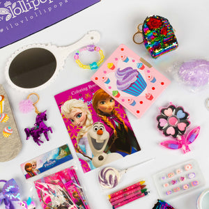 There is a cupcake journal, a purple princess braid, a Lollipopa Birthday Box, a white mirror, a bracelet with purple, pink, and yellow, a purple sequin horse keychain, a Disney Frozen coloring book with Elsa, Anna, and Olaf, a colorful sequin mini backpack keychain, a flower makeup set, a set of 3d press on nails, crayons, and a birthday squishy.