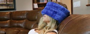 Young woman soothing her migraine or sinus headache with the microwavable Huggaroo headache aromatherapy wrap